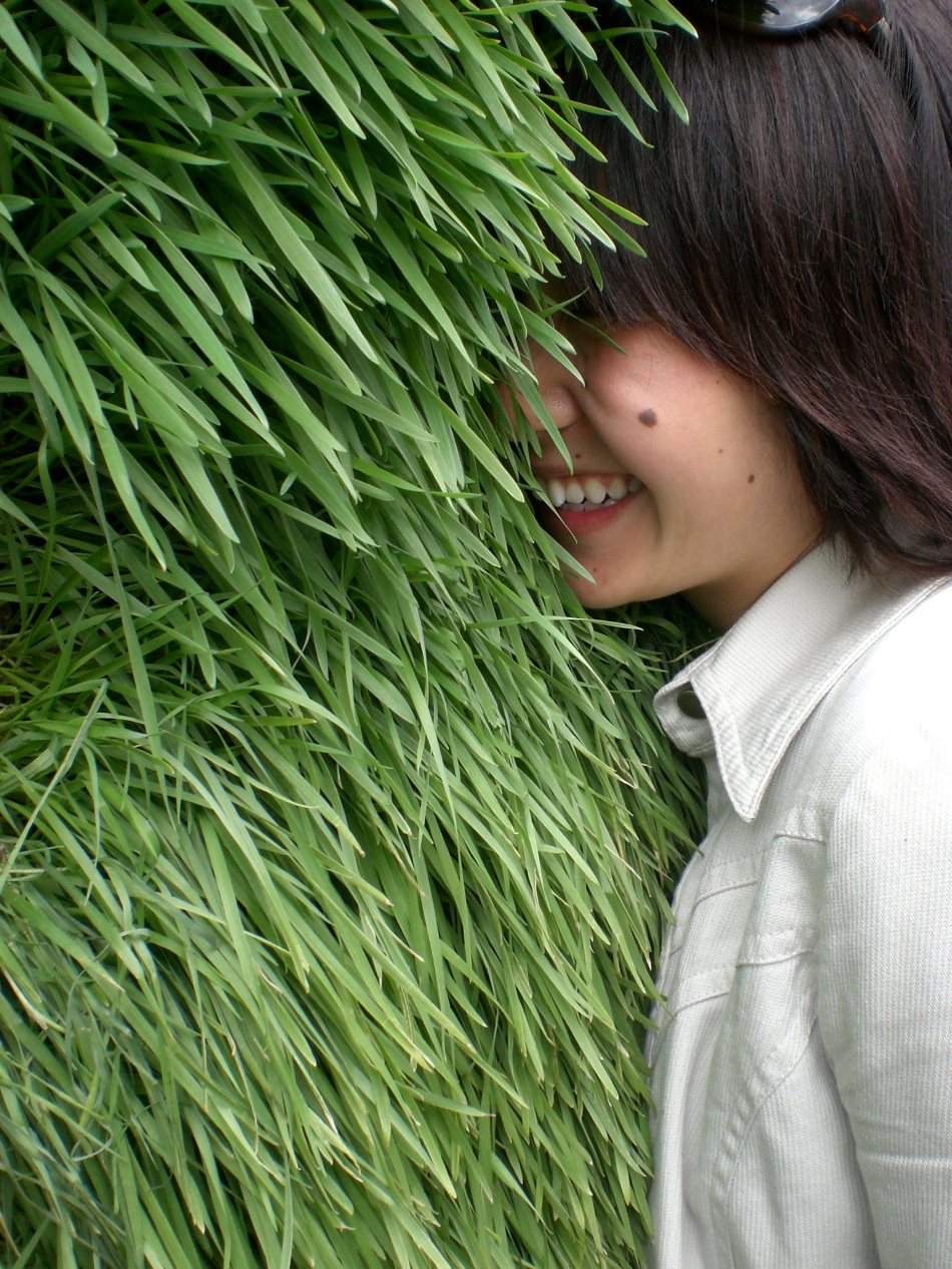 Picture of Lian Chikako Chang smiling, with her face buried in a wall of well-kept green grass.